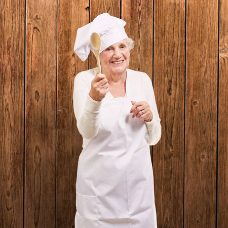 portrait of senior cook woman holding a wooden spoon against a wooden wall photo
