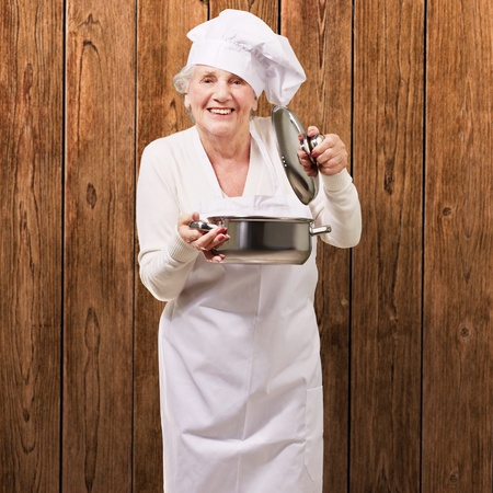 portrait of cook senior woman opening sauce pan against a wooden wall photo