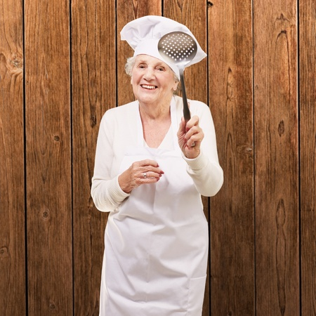 portrait of sweet senior cook woman holding a metal spoon against a wooden wall photo