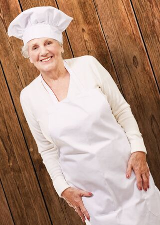 portrait of cook senior woman smiling against a wooden wall Stock Photo - 13280334