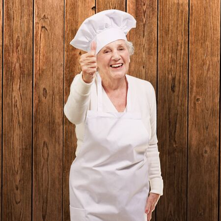 portrait of cook senior woman doing good gesture against a wooden wall Stock Photo - 13280219