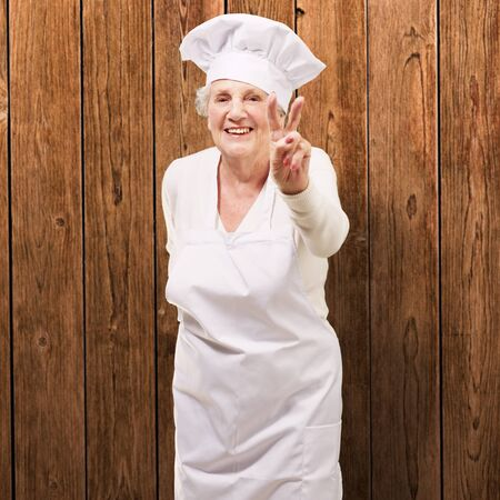 portrait of cook senior woman doing good gesture against a wooden wall photo