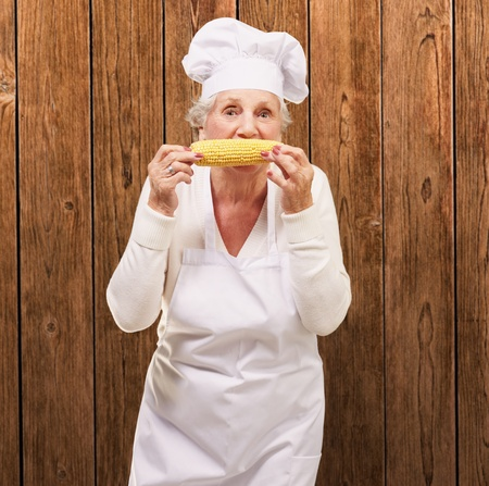 portrait of senior cook woman eating corn cob over wooden wall Stock Photo - 13280228