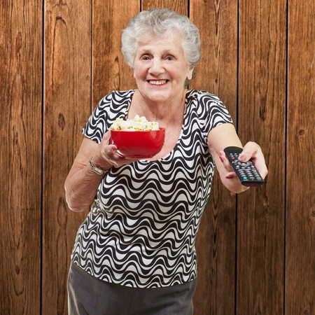 portrait of happy senior woman looking the tv against a wooden wall Stock Photo - 13280192