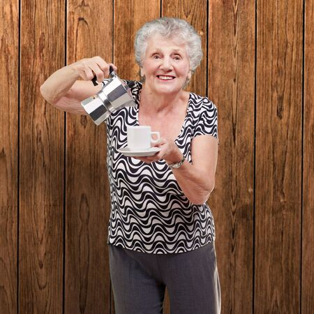 portrait of a vitality senior woman serving a tea cup against a wooden wall photo