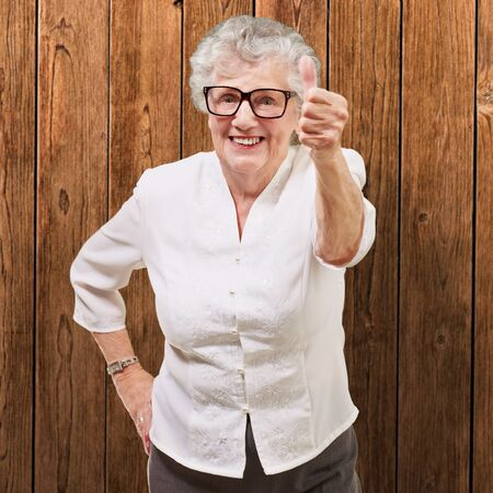portrait of adorable senior woman doing good gesture against a wooden wall Stock Photo - 13280197