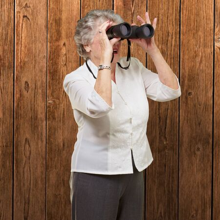 portrait of senior woman looking through a binoculars against a wooden wall photo