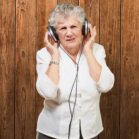 portrait of senior woman listening to music against a wooden wall photo