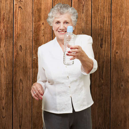 portrait of healthy senior woman holding a water bottle against a wooden wall photo