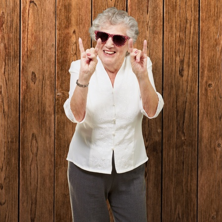 portrait of a happy senior woman doing rock symbol against a wooden wall Stock Photo - 13280257