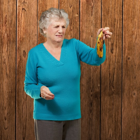 Senior woman holding a rotten banana against a wooden background photo