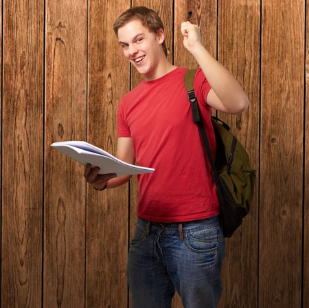 portrait of handsome student holding notebook and pen against a wooden wall photo