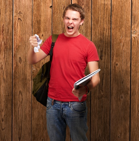 young angry student man roughing a sheet against a wooden wall photo