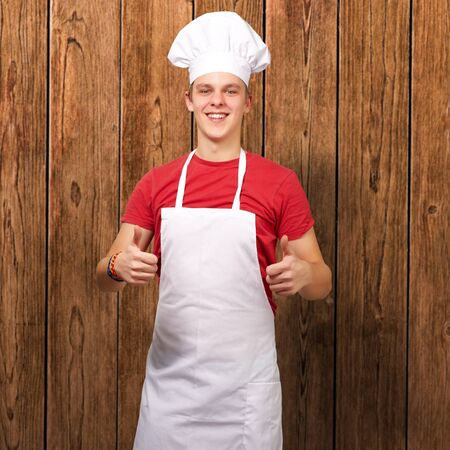 portrait of young cook man doing success symbol against a wooden wall Stock Photo - 13280324