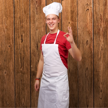 portrait of young cook man doing success symbol against a wooden wall photo