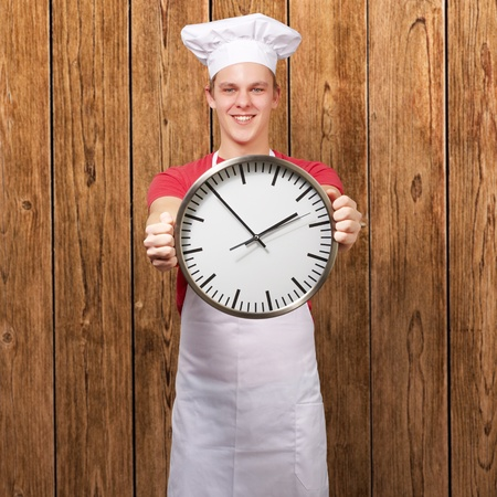 portrait of young cook man holding clock against a wooden wall photo