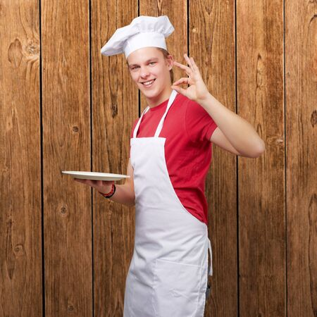 portrait of young cook man against a wooden wall photo