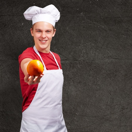 portrait of young cook man offering orange against a grunge wall photo