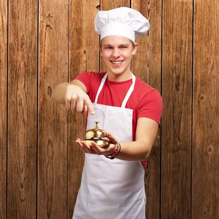 portrait of young cook man pressing a golden bell against a wooden wall photo