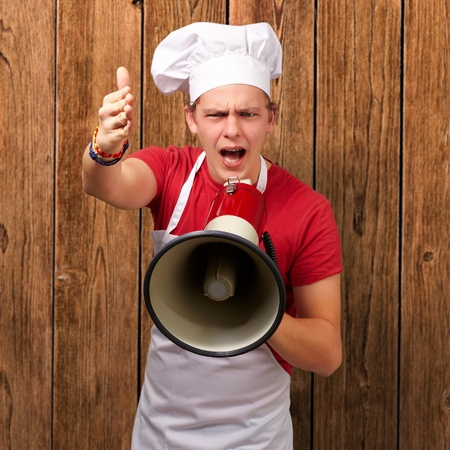 portrait of young cook man screaming with megaphone and gesturing against a wooden wall photo
