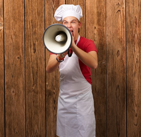 portrait of young cook man screaming with megaphone against a wooden wall photo