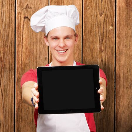 portrait of young cook man showing a digital tablet against a wooden wall photo