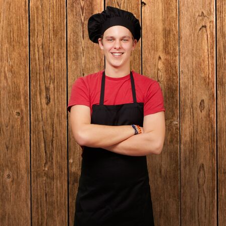 portrait of young cook man wearing uniform and smiling against a wooden wall photo