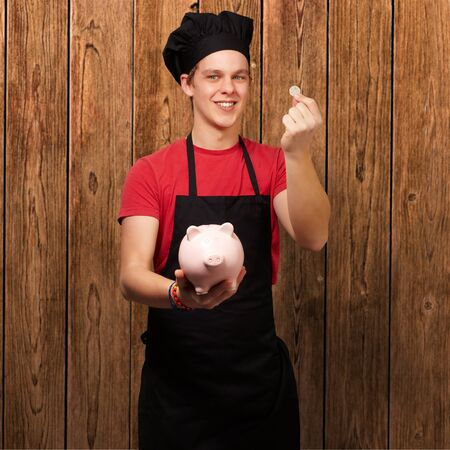 pink hat: portrait of young cook man holding euro coin and piggy bank against a wooden wall