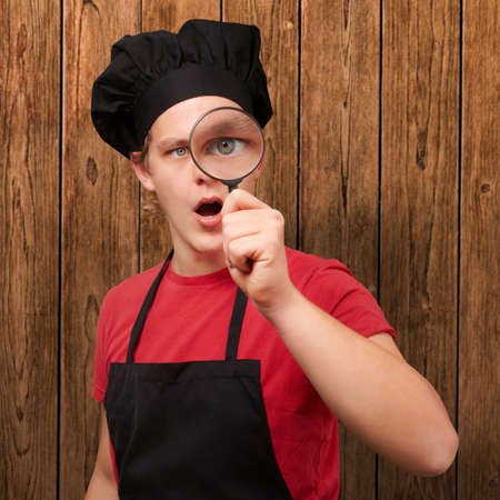 portrait of young cook man looking through a magnifying glass against a wooden wall photo