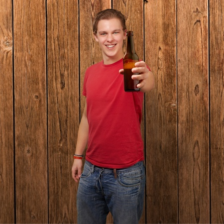 single beer: portrait of young man holding beer against a wooden wall Stock Photo