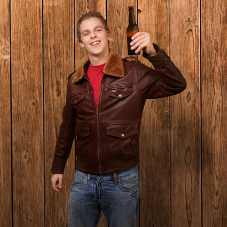 portrait of young man holding beer against a wooden wall photo