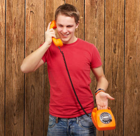 portrait of young man talking on vintage telephone against a wooden wall photo