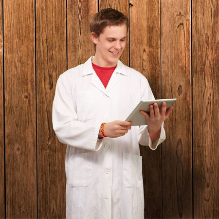 portrait of young academic holding a digital tablet against a wooden wall photo
