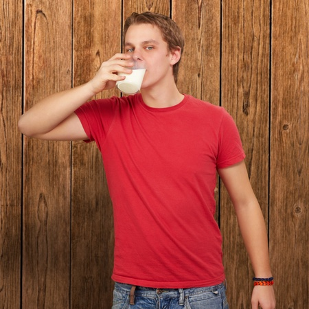 portrait of young man drinking milk against a wooden wall photo