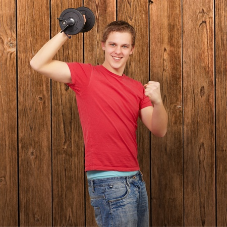 young man doing fitness with weights against a wooden wall photo