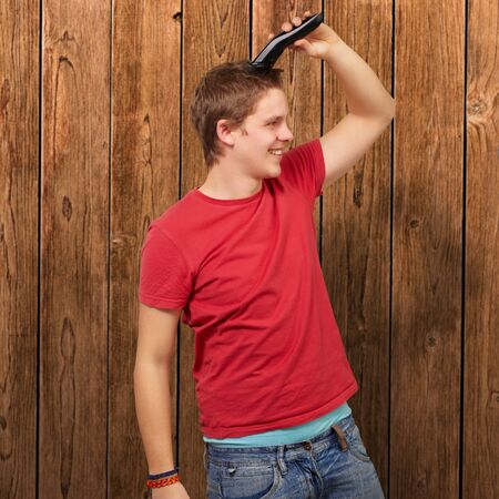 portrait of young man cutting his hair against a wooden wall photo
