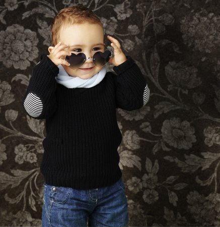 young boy with heart sunglasses against a vintage background Stock Photo - 13485730