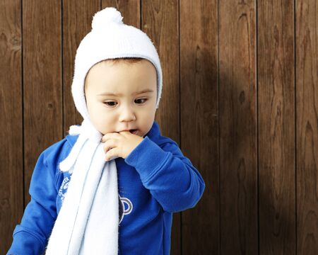 young boy with his finger in his mouth against a wooden background Stock Photo - 13485699