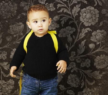 niño con mochila: joven con una mochila en un contexto de época Foto de archivo