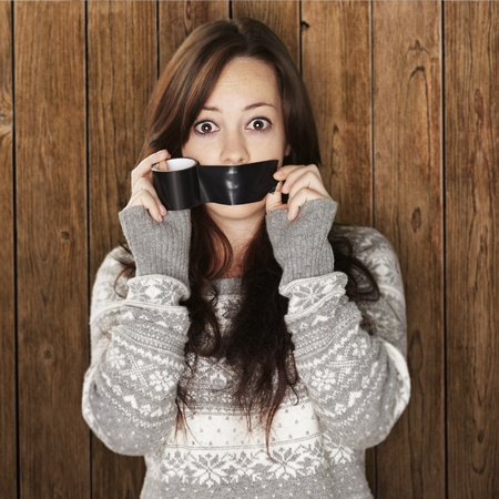 silenced: young woman covering her mouth with black tape
