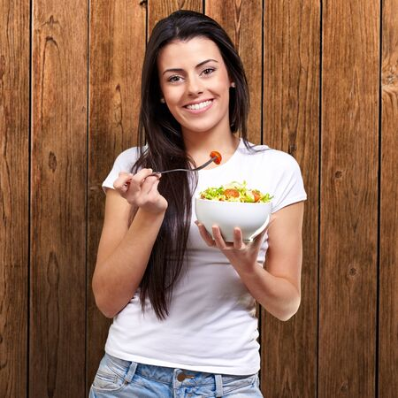 portrait of healthy woman eating salad against a wooden wall Stock Photo - 13280152