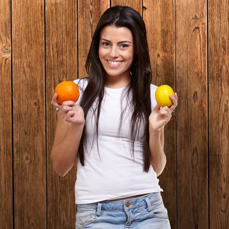 young pretty girl holding orange and lemon against a wooden wall photo