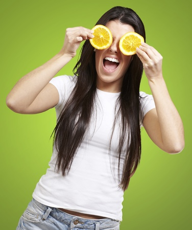 woman with orange slices as eyes against a green background photo