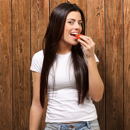portrait of young woman eating strawberry against a wooden wall photo