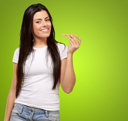 portrait of young woman eating cereal bar over green background photo