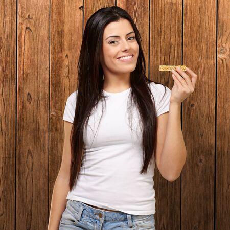 barra de cereal: retrato de una mujer joven que come una barra de cereal contra una pared de madera