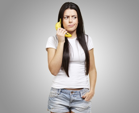 woman holding a banana as a telephone against a grey background photo