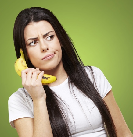 woman holding a banana as a telephone against a green background photo