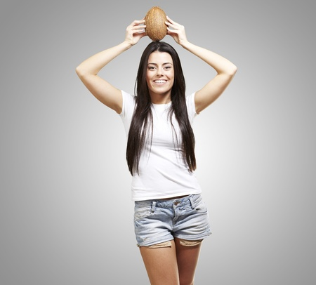 young girl holding a coconut on her head against a grey background photo
