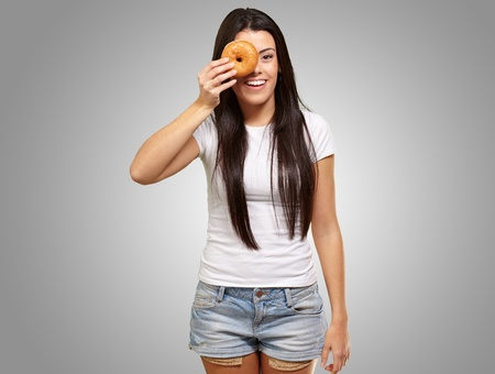 portrait of young woman looking through a donut over grey Stock Photo - 13280252